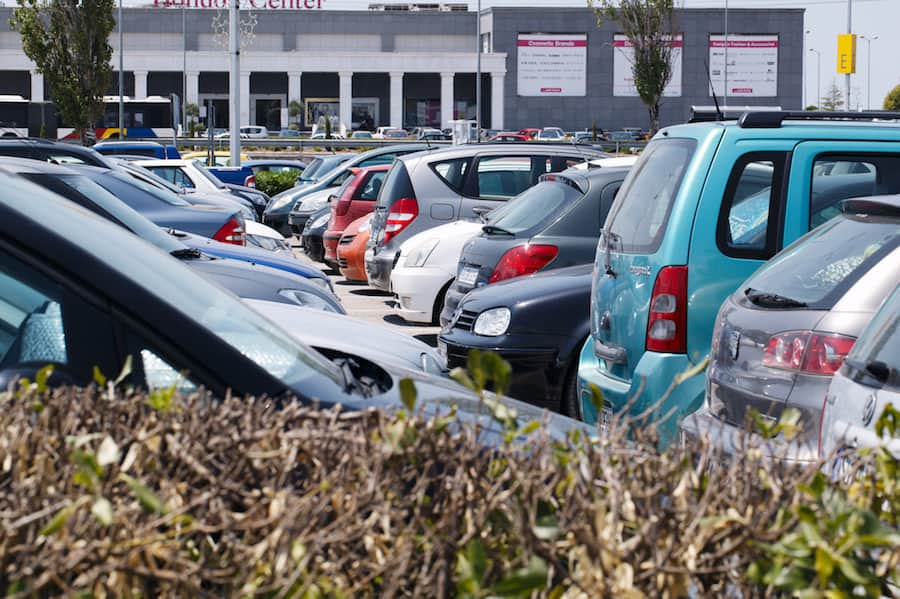 THESSALONIKI, GREECE - AUGUST 1, 2013: View over a hedge of tightly packed cars parked in an open-air car park in the sunshine in front of a commercial building