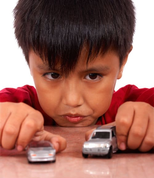 Small Boy Preoccupied Playing Toy Cars